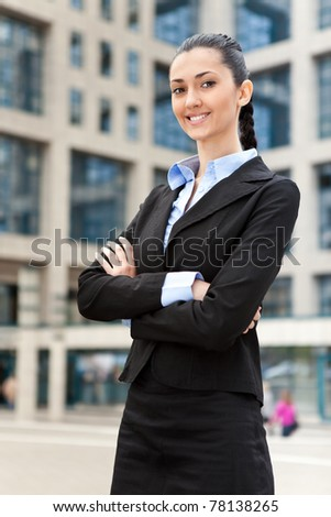 businesswoman standing outdoors by building smiling - stock photo