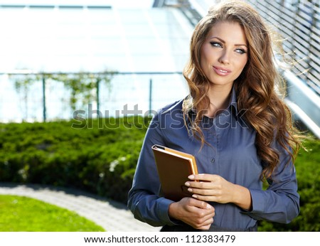 Businesswoman standing outside a modern house - stock photo