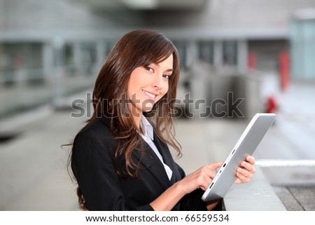Businesswoman standing outside with electronic tab - stock photo