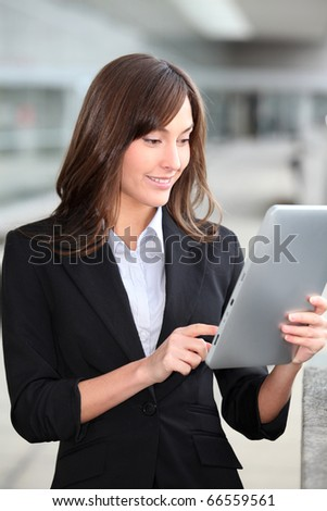 Businesswoman standing outside with electronic tab