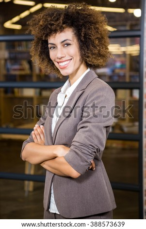 Businesswoman standing with arms crossed in office