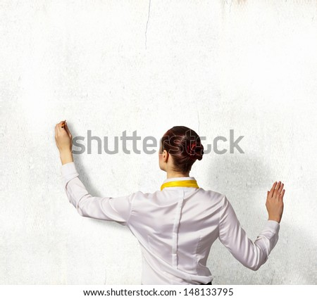 Businesswoman standing with back drawing on blank wall - stock photo