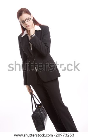 Businesswoman standing with purse and hand to her face thinking
