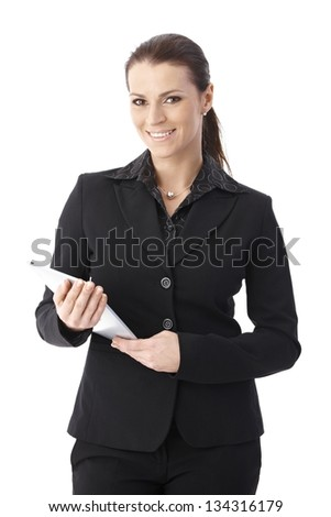 Businesswoman standing with touchscreen computer handheld, smiling at camera, studio portrait. - stock photo
