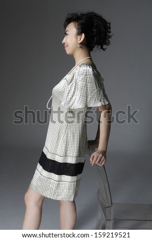 Businesswoman stands near a chair thinking of something at the gray background