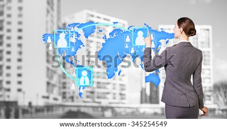 Businesswoman stands near map with icons on the city background. Elements of this image furnished by NASA