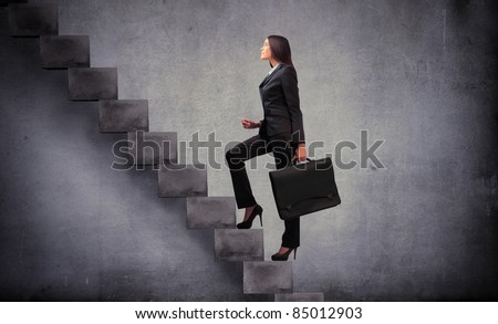 Businesswoman stepping up a stairway - stock photo