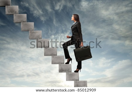 Businesswoman stepping up a stairway with sky in the background - stock photo
