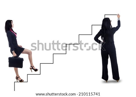 Businesswoman stepping up on stairs to gain her success with partner draw the way - stock photo