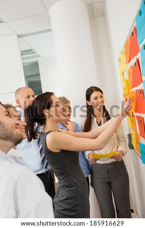 Businesswoman sticking labels on whiteboard during meeting - stock photo