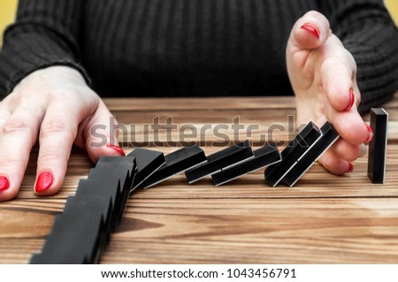 Businesswoman stopping domino effect. Problem solving concept.