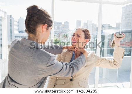 Businesswoman strangling her partner holding a shoe in bright office - stock photo