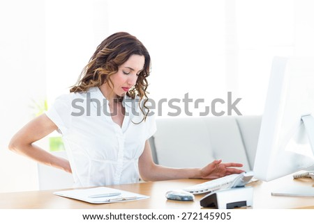 Businesswoman suffering from backache on white background - stock photo