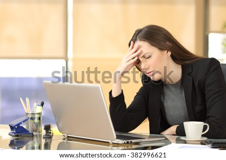 Businesswoman suffering migraines at job working on line with a laptop sitting in a desktop at office - stock photo