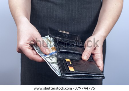 Businesswoman takes out dollars from leather wallet. Conception of safe storage and protection of cash. Financial theme.  - stock photo