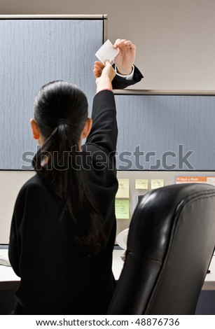 Businesswoman taking note from next cubicle - stock photo