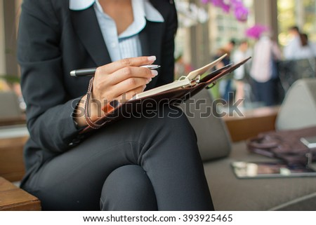Businesswoman taking notes during waiting at hotel lobby.