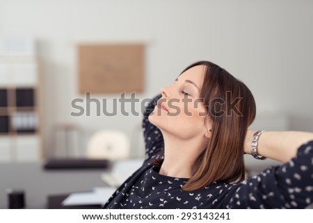 Businesswoman taking time out at work relaxing in her chair at the office with her head tilted back on her clasped hands and eyes closed - stock photo