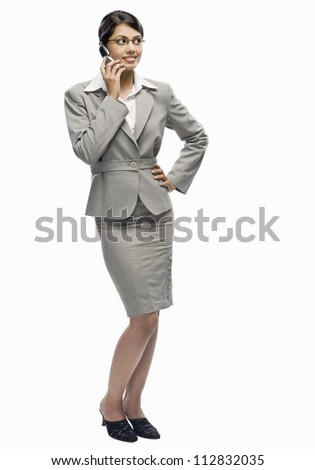 Businesswoman talking on a mobile phone against a white background