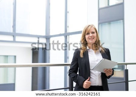 businesswoman talking on a mobile phone & tablet at the office - stock photo