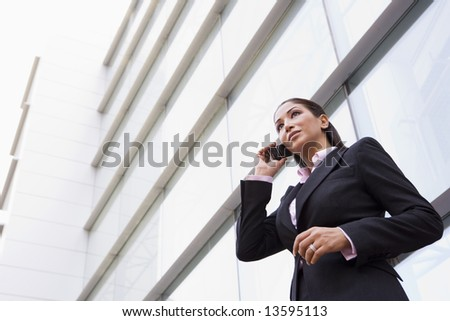 Businesswoman talking on cell phone outside modern office building - stock photo