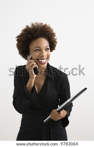 Businesswoman talking on cellphone smiling against white background.