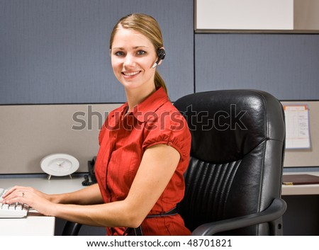 Businesswoman talking on headset at desk - stock photo