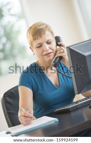 Businesswoman talking on landline phone at the office
