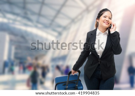 businesswoman talking on mobile phone while carrying luggage at airport - stock photo