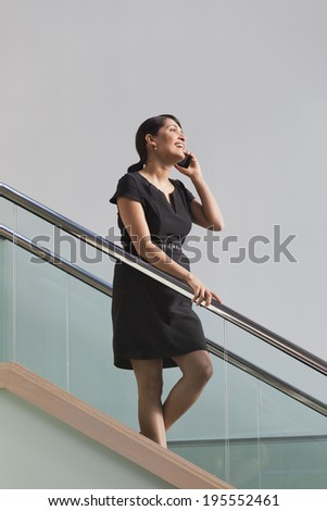 Businesswoman talking on mobile phone while walking down stairs