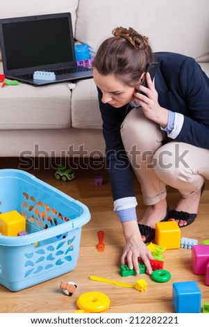 Businesswoman talking on phone and picking up toys - stock photo
