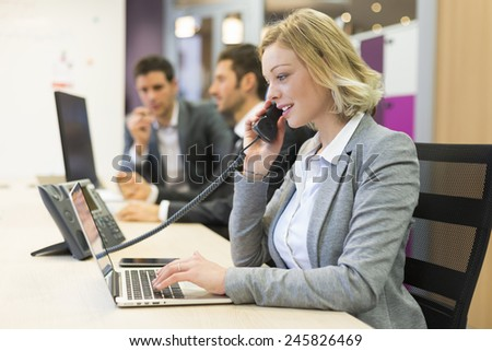 Businesswoman talking on the phone in modern office - stock photo