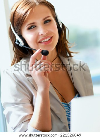 businesswoman talking on the phone while working on her compute - stock photo