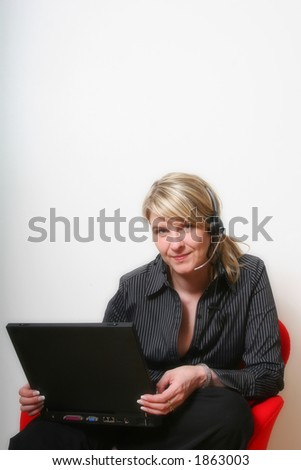 Businesswoman talking on the phone, with laptop and a headset