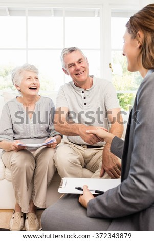 Businesswoman talking with senior couple at home - stock photo