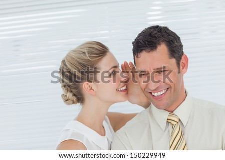 Businesswoman telling secret to her colleague in bright office - stock photo