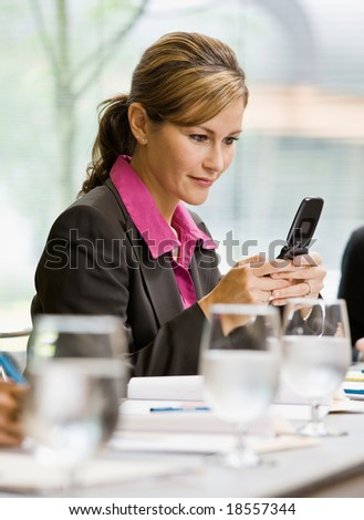 Businesswoman text messaging on cell phone in conference room - stock photo