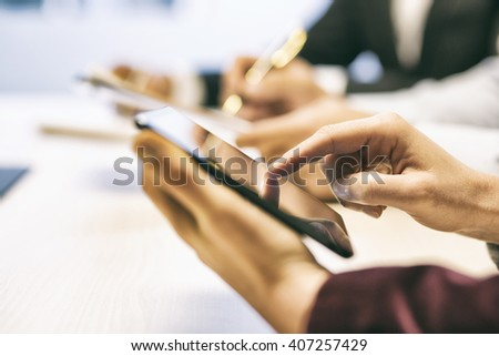 Businesswoman texting on cell phone during a meeting. Close-up hands - stock photo