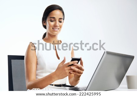 Businesswoman texting on mobile phone in office at desk with laptop computer - stock photo