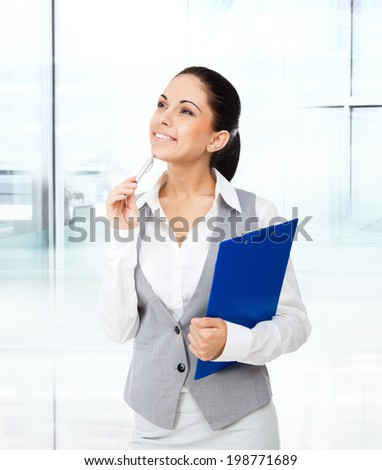 Businesswoman think looking up to empty copy space, young attractive business woman think, idea, hold folder pen on chin. concept pondering in modern office
