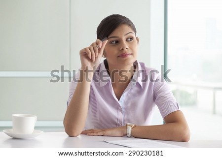 Businesswoman thinking while preparing new project - stock photo