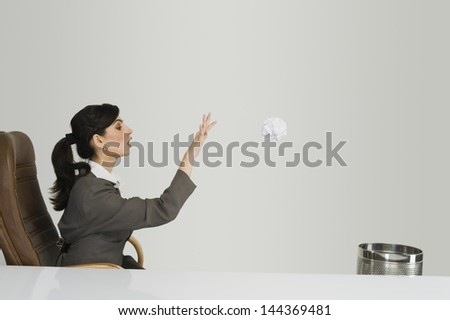 Businesswoman throwing crumpled paper into a wastepaper basket - stock photo
