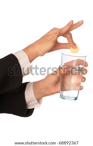 Businesswoman throws a vitamin pill to the glass with water