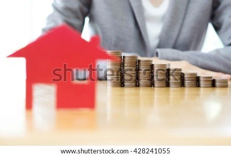 businesswoman to stack of coins and red house blackground