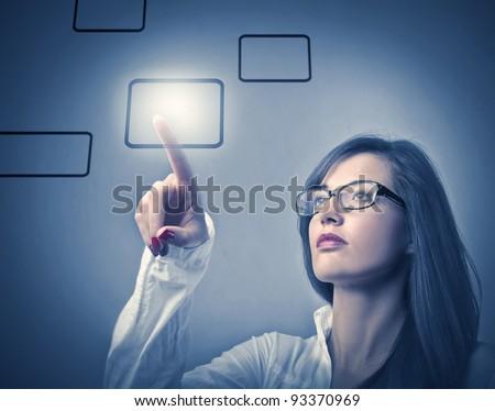 Businesswoman touching a button on a touchscreen - stock photo