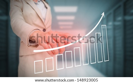 Businesswoman touching bar chart and arrow graphic in data center