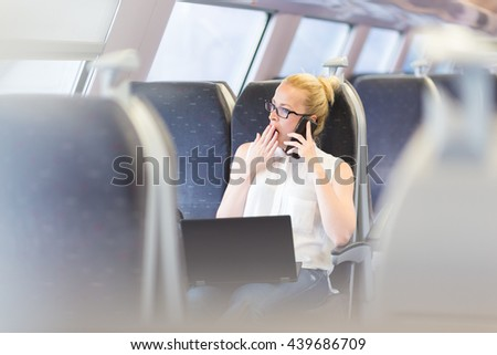 Businesswoman traveling by train, yawning while talking on cellphone and working on laptop. Long and tiresome business travel concept. - stock photo