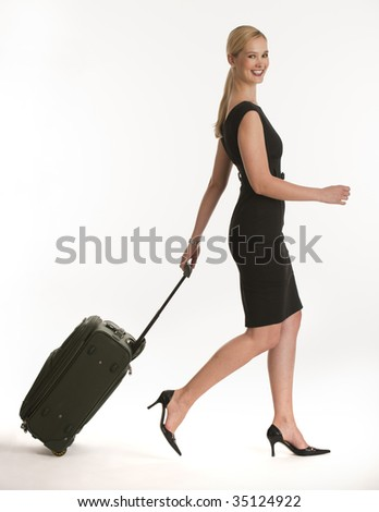 businesswoman traveling with rolling suitcase on white seamless background