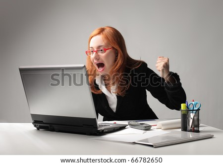 Businesswoman triumphing in front of a laptop - stock photo