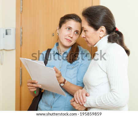 businesswoman trying to collect money from mature housewife - stock photo